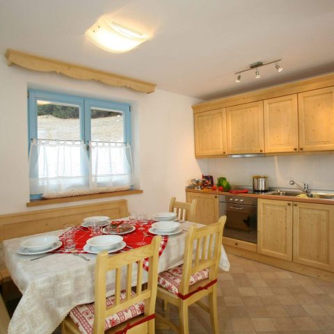 Kitchen corner furnished in ladin style, with baked clay-glass cooker, dishwasher, oven, microwave oven