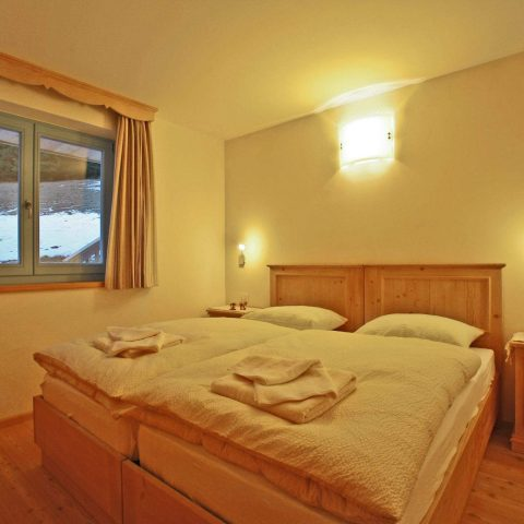 Comfortable double bed bedroom with fir wood furniture and yellow clay wall to keep a steady humidity