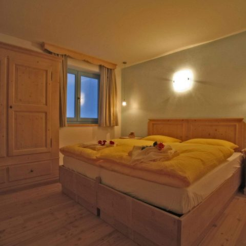 Double bed bedroom with larch floor and sky-blue clay wall to keep a steady humidity