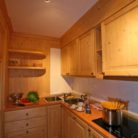Kitchen corner made of massive fir wood with dishwasher, fridge, baked clay-glass cooker