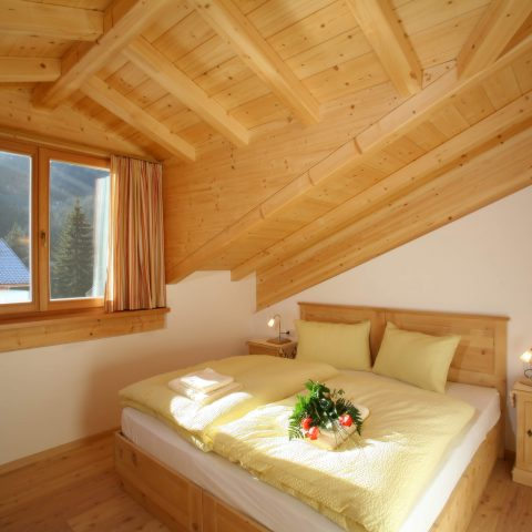 Comfortable double bed bedroom furnished in cembran pine and larch floor. Wide window with a wonderful view on the Colac